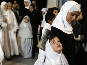 Teacher Mervat Ballut with Lila Mahmoud, 7, observe Hajj Day at Toledo Islamic Academy.