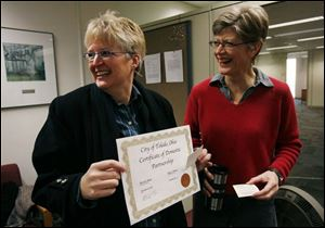 Kim Welter, left, and Merri Bame display their certificate. They arrived yesterday before Carol Bresnahan and Michelle Stecker at Government Center, but ceded their place in line.