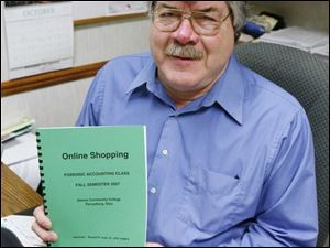 Ronald Coon, an adjunct instructor of accounting at Owens Community College, displays the guide that he and his class put together on how to avoid getting involved in Internet scams.