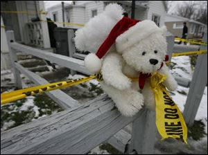 Stuffed animals were placed along the fence in front of the home along with a banner offering prayers for the family.