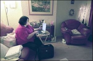 Karen Torley, 41, does casework on her laptop as she watches television and takes phone calls in her home in Glasgow. Ms. Torley began the campaign to free inmate Kenneth Richey.