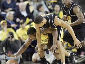 Michigan forward DeShawn Sims reaches for the ball in a battle with Iowa guard Tony Freeman. Sims scored 18 points.