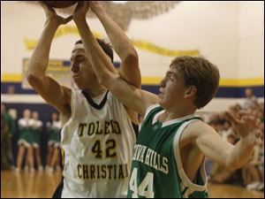 Toledo Christian s Ethan Michael, left, and Ottawa Hills  Philip Beans fight for a rebound.Michael averages 13.4 points. Beans averages 18.4 points and leads the TAAC in reboundng (11.9).