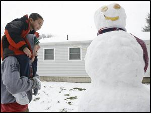 There was enough snow for a snowman on Maumee's Shelly Avenue where Taylor Monus, 17, carries Blake Olvear, 6.
