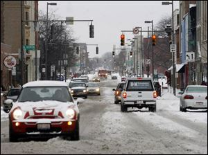 Adams Street in downtown Toledo was snow-covered Friday morning. No major injury crashes were reported in the region.