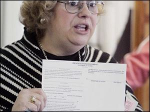 Jill Kelly, director of the Lucas County Board of Elections, holds an identification envelope in which an absentee ballot must be received to be counted. The elections board is holding several meetings in the county to familiarize voters with the balloting process before Ohio's March 4 primary.