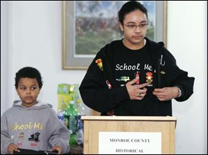 "NBRN pride07p  02/02/08  The Blade/Dave Zapotosky Caption: Tevyn Cole, 15,  talks about his School Me line of clothing at the opening of  Pride and Oppression: a Celebration of Black History Month, at the Monroe County Historical Museum, in Monroe, Mich., on Saturday, February 2, 2008. His brother, Donovan Cleggett, 8, models some of his clothing, left.  Tevyn is a freshman at Milan High School.  His clothing featuring inventions by African Americans,  is ""designed to inspire and motivate today's youth to recognize the achievements of those before them."" Summary: Please get shots during this event: The Monroe County Historical Museum, 126 S. Monroe St., will feature Pride and Oppression: a Celebration of Black History Month, as a special exhibit during February 2008. The grand opening celebration is 1 p.m. Feb. 2.  Tevyn Cole, a freshman at Milan High School, also will give a lecture on Feb. 2."