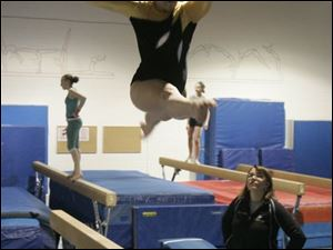 Perrysburg senior Macy Nordhaus practices on the balance beam under the watch of Michelle Nordhaus, her mother and coach. Macy qualfied for state in three events last year.
