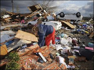 Colleen Conner sifts through the debris of her friend Bonnie Scott s house. Both women escaped serious injury. (ASSOCIATED PRESS)