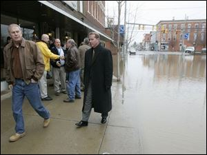 Gov. Ted Strickland surveys Main Street in Ottawa, flooded by the Auglaize and Blanchard rivers. He also visited Findlay, where 500 homes were damaged. (THE BLADE/DAVE ZAPOTOSKY)
