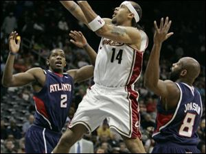 The Cavaliers' Ira Newble drives between Atlanta's Joe Johnson, left, and Anthony Johnson. Newble scored a season-high 18.