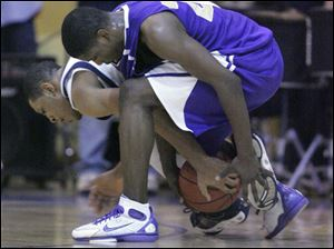 Khari Riley, right, who led Waite with 22 points and 10 rebounds, battles for a loose ball with Whitmer s Antwan