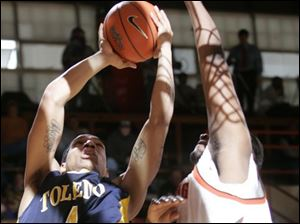 The long arm of Bowling Green's Otis Polk makes it difficult for Toledo's Jonathan Amos to get off a shot. Polk, a 6-9 sophomore, had 12 points, 5 rebounds and four blocked shots.