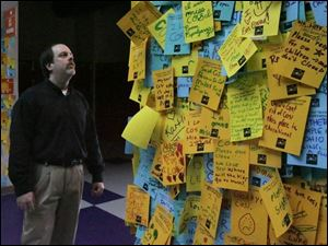 COSI's director of exhibits, Carl Nelson, reads the 'memory wall' only a little bit at a time because it saddens him.