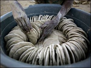 Dried mud cookies are arranged for sale in Port-au-Prince, Haiti. They are made from dirt, salt, and vegetable oil.
