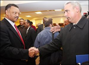 The Rev. Jesse Jackson shakes hands with John Nixon, president of the City Council, during his visit to Lima yesterday. (THE BLADE/AMY E. VOIGT)