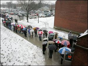 Hundreds of people line up outside the Toledo Technology Academy, where they hoped to see former President Bill Clinton.