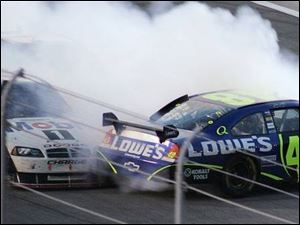Sam Hornish Jr., left, and Jimmie Johnson make contact with just over 20 laps to go in the