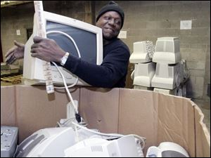 Collois Coachman prepares computers and printers in the Goodwill Industries warehouse for shipment to be recycled.