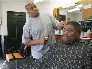 Barber Ray Oliver trims Keith Harris' hair at Tapers Barber Shop, a good place to catch up on local history.