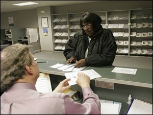 Tom Hojnacki handles questions from taxpayer Virgaie Washington at the IRS offices in downtown Toledo.