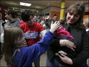 Humane Society volunteer Nora Solomon holds Spock for admirers Kortney Gonyer of Wayne, Ohio, and Stacy Smith of Luckey, Ohio.