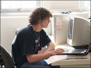 Andy Kissling uses a computer to design schematics for the school buildings.