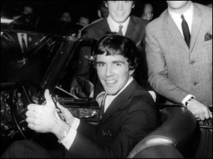 Dave Clark, gives a thumb's up sitting in a Bentley Continental, with the other members of the band Dave Clark Five band, Dennis Payton and Mike Smith, right, at the In