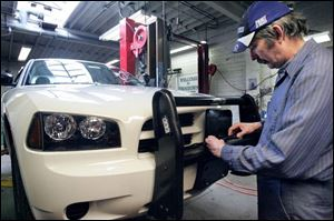 Bob Keel installs equipment on a police car at the fleet service station on Spielbusch Avenue.
