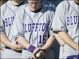Sophomore A.J. Ramthum (16) and his teammates take a moment to mark the one-year anniversary of the bus crash that killed five Bluffton baseball players on March 2, 2007.