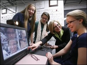 Sisters Valeri Wolf, 16, and Rachel Wolf, 13, watch as Mary Nyitray of Optical Arts shows Amelia Wolf, 16.