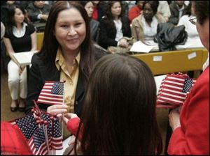 Kenya native Jacqueline Therese Busch receives her flag during the naturalization ceremony at the University of Toledo college of law where 81 immigrants became citizens.
