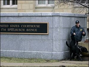 A U.S. Marshall with a dog conducts a security check around the federal courthouse in Toledo on Tuesday morning. The trial of three men on trial for for terrorism conspiracy charges started Tuesday. (THE BLADE/DAVE ZAPOTOSKY)
