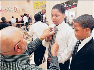Ronald Thompson, ex-CEO of Midwest Stamping and Manufacturing, fixes Kemon Thorton's tie. Alontay Gould watches.