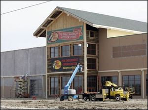 The 150,000-square-foot outdoors store, under construction in Rossford, is to open in the middle of June. Like its rival in Dundee, Mich., the chain is considered a tourist destination.