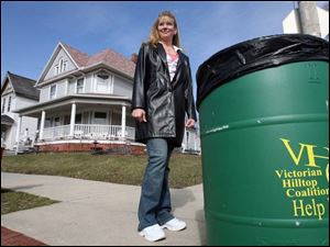East Toledo community activist Gail Wahl, left, says placing large trash cans like this one on local streets has helped kee
