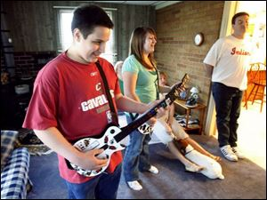 Jacob Tanner, left, of Maumee and his sister Marissa play a video game while their family watches. Jacob, 16, was 18 months old when he first showed signs of autism.