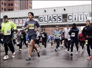Most of these runners bundle up against the 35-degree temperatures at the start of the Glass City Marathon, en route toward the Perrysburg-Maumee bridge, the halfway point of the race.