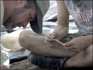 Brian Redmond, left, of the Cleveland Museum of Natural History brushes soil from artifacts at the site in 2004.