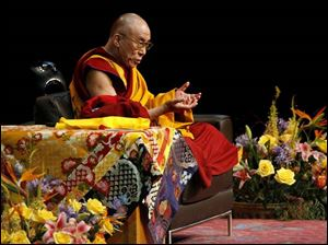Wearing his traditional robe and sitting cross-legged, His Holiness the Dalai Lama talks to a sold-out crowd at Crisler Arena.