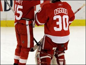 Red Wings winger Darren McCarty, left, congratulates goalie