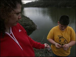 Sue Billingsley watches as Austyn Underwood, 13, of Oak Harbor puts a worm on her line so that she can fish in Silver Lake during the Welcome Back Walleye celebration in the park.
