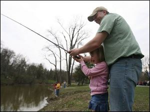 Erik Young of Perrysburg helps daughter Kelsi, 6, cast her line into Silver Lake while taking part in the park event.