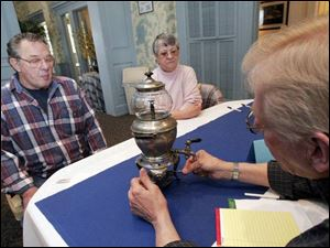 Roy and Shirley Brown await an appraisal on an old coffeemaker from Harry Tennery during a local version of &#39
