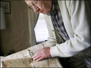 Frank Basler studies a map showing the route he traveled in Europe where he was a tank driver during World War II.
