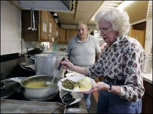 Terry and Kathryn Rathbun, serving lunch at the community center, say the all-volunteer soup kitchen is struggling as donations dwindle. The center serves hot meals three days a week.