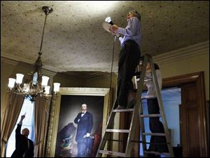 Albert Albano, executive director of the Cleveland-based Intermuseum Conservation Association, and Emily Helwig, a paper conservator, examine the drawing room ceiling.