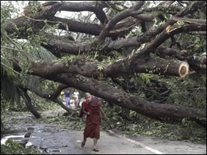 A Myanmar Buddhist Monk makes his way past a fallen tree following a devastating cyclone on Sunday, in Yangon. The death toll from the cyclone has risen to almost 4,000, a Myanmar state radio station has said.