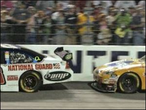 Dale Earnhardt Jr. leads Kyle Busch, moments before an accident that sent Earnhardt into the wall and to a 15th-place finish.