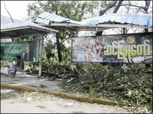 Residents sit at a bus station among debris left by the weekend's devastating cyclone on Tuesday, in Yangon, Myanmar. (ASSOCIATED PRESS)
